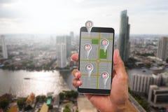 Wręcza mienie telefon komórkowego z mapą i nawigacja symbol na ekranie na zamazanym miasta tle Fotografia Royalty Free