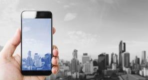 Wręcza mieniu mobilnego mądrze telefon, czarny i biały miasta tło Zdjęcia Royalty Free