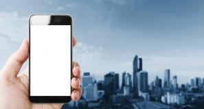 Wręcza mieniu mobilnego mądrze telefon, pusty bielu ekran, błękitny miasta tło Obrazy Royalty Free