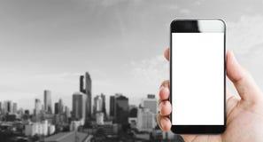 Wręcza mieniu mobilnego mądrze telefon, pusty bielu ekran, czarny i biały miasta tło Obrazy Stock