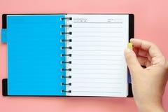 Wręcza obracać pustą stronę notatnik na różowym tle obrazy royalty free