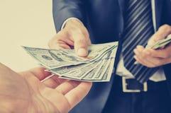 Wręcza odbiorczego pieniądze, dolarów amerykańskich rachunki od biznesmen ręki, (USD) Fotografia Royalty Free