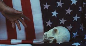 Wręcza patroszonego czaszka na tle flaga amerykańska Fotografia Stock