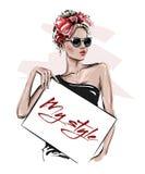 Wręcza patroszonej pięknej młodej kobiety trzyma plakat w okularach przeciwsłonecznych Elegancka dziewczyna z łękiem na jej głowi obraz royalty free