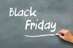 Wręcza pisać Black Friday z kredą na chalkboard Fotografia Royalty Free