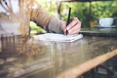 Wręcza pisać puszku na pustym notatniku na drewnianym stole obrazy stock