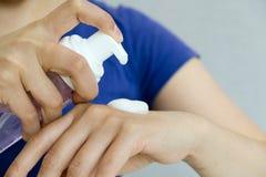 Wręcza prasowej pompy piany cleanser butelkę z plamy łazienki tłem pojęcie higiena, mousse stawiać pomaduje na ręce Obraz Royalty Free