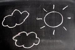 Wręcza rysunek biel kreda w słońca i chmury kształcie na czerni deski tle ilustracji