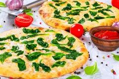 Wręcza rzucanemu szpinakowi serową pizzę na pergaminowym papierze Obraz Stock
