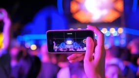 Wręcza sylwetce magnetofonowego wideo muzyka na żywo rockowy koncert z smartphone zdjęcie wideo