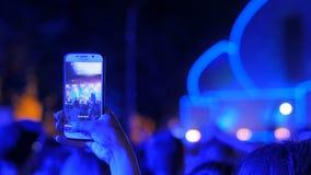 Wręcza sylwetce magnetofonowego wideo muzyka na żywo rockowy koncert z smartphone zbiory