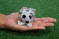 Wręcza trzymać akrylowego futbolowego sześcian na sztucznej trawie Obraz Stock
