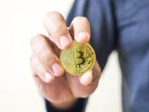 Wręcza trzymać elektroniczną monetę z złocistymi monetami na wierzchołku pomysł †‹â€ ‹oszczędzania pieniądze dla przyszłości je obraz stock