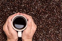 Wręcza trzymać filiżankę czarna kawa i piec kawowe fasole rywalizuje Fotografia Royalty Free