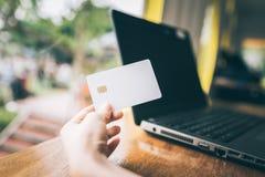 Wręcza trzymać kredytową kartę z laptopem w tle Obrazy Royalty Free