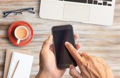 Wręcza trzymać mądrze telefon i drewnianego biurowego biurka stół Zdjęcie Stock