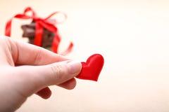 Wręcza trzymać małego serce i czekoladę z faborkiem Obrazy Stock