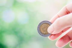 Wręcza trzymać monetę, 10 bahtów waluty Tajlandzki pieniądze Fotografia Royalty Free