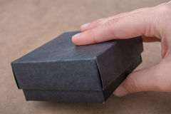 Wręcza trzymać prezenta pudełko czarny kolor Zdjęcia Stock