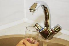 Wręcza trzymać szkło nalewający od kuchennego faucet woda Zdjęcia Royalty Free