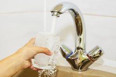 Wręcza trzymać szkło nalewający od kuchennego faucet woda Obraz Royalty Free