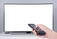Wręcza trzymać TV pilot do tv z DOWODZONYM TV i bielu ekranem Zdjęcie Stock