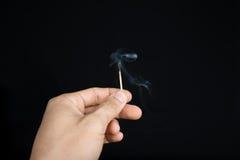 Wręcza trzymać wygasłego matchstick na czarnym tle Obraz Stock