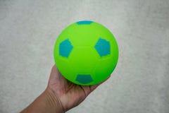 Wręcza trzymać zieleni i błękita piłki nożnej piłkę fotografia royalty free