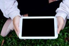 Wręcza używać pustego ekranu pastylkę nad zielonych traw tłem Zdjęcie Royalty Free