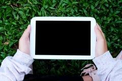 Wręcza używać pustego ekranu pastylkę nad zielonych traw tłem Zdjęcia Royalty Free