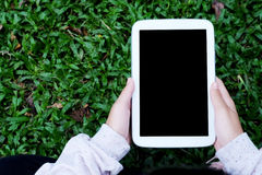 Wręcza używać pustego ekranu pastylkę nad zielonych traw tłem, mo Fotografia Stock