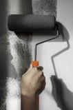 Wręcza używać rolkową farbę stosuje popielatą farbę na biel ścianie Obraz Royalty Free