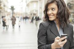 wręcza ulicznej chodzącej kobiety smartphone Obrazy Royalty Free