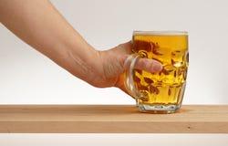 Wręcza wp8lywy szkło lekki piwo od drewnianej deski Zdjęcia Royalty Free