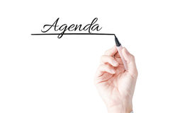 Wręcza writing agendę z błękitnym markierem na przejrzystej desce Zdjęcia Stock