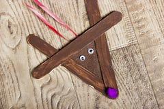 Wręcza wykonującego ręcznie popsicle renifera, kłaść na drewnianym zbożowym tle Fotografia Stock