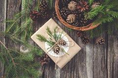 Wręcza wykonującego ręcznie prezent na nieociosanym drewnianym tle i kosz z jodła rożkami i gałąź Obraz Royalty Free