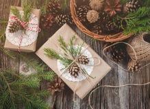 Wręcza wykonującego ręcznie prezent na nieociosanym drewnianym tle i kosz z jodeł gałąź i rożkami, odgórny widok Obrazy Stock