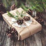 Wręcza wykonującego ręcznie prezent na nieociosanym drewnianym tle z Zdjęcia Stock