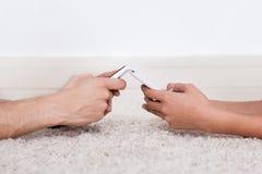 Wręcza wysylanie sms przez smartphones na dywaniku Obraz Royalty Free