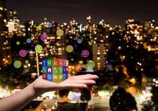 wręcza z zastosowanie ikon sześcianem na nim Zamazany miasto przy nocą Fotografia Royalty Free