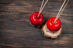 Wręcza zamaczającego karmelu jabłka zakrywającego z wielo- kolorem kropi Zdjęcia Stock