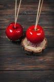 Wręcza zamaczającego karmelu jabłka zakrywającego z wielo- kolorem kropi Fotografia Royalty Free