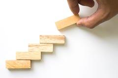 Wręcza aranging drewnianego bloku sztaplowanie jako kroka schodek Obraz Stock