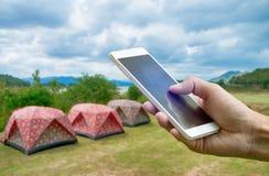 Wręcza hoding smartphone na zamazanym Namiotowym campingu przy Keang Kra Jan Zdjęcie Royalty Free