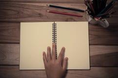Wręcza i notatnik na drewnianym stole Obrazy Stock