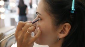 Wr?cza makija?u artysty stosowa? makeup na twarzy m?oda kobieta Dziewczyna robi oka makeup w fachowym salonie r?wno zbiory wideo
