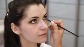 Wr?cza makija?u artysty stosowa? makeup na twarzy m?oda kobieta Dziewczyna robi oka makeup w fachowym salonie r?wno zdjęcie wideo