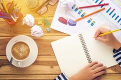 Wręcza writing w otwartym notatniku na stole przy rankiem Obraz Stock