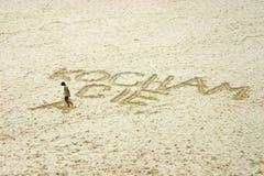 Wraiting on sand. Teenager writing on sand \J love you Stock Image